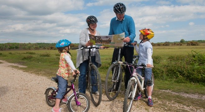 A family group on bikes with a map on a gravel path