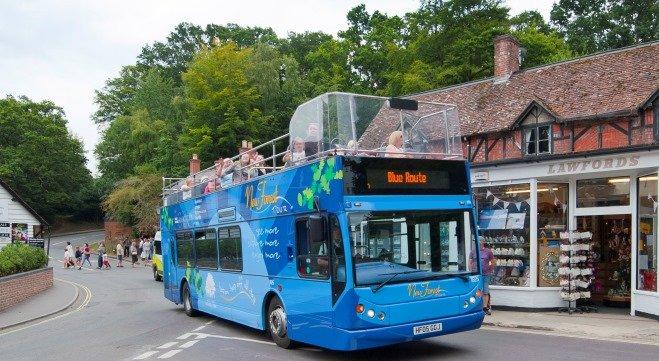A bright blue tour bus travels through a village