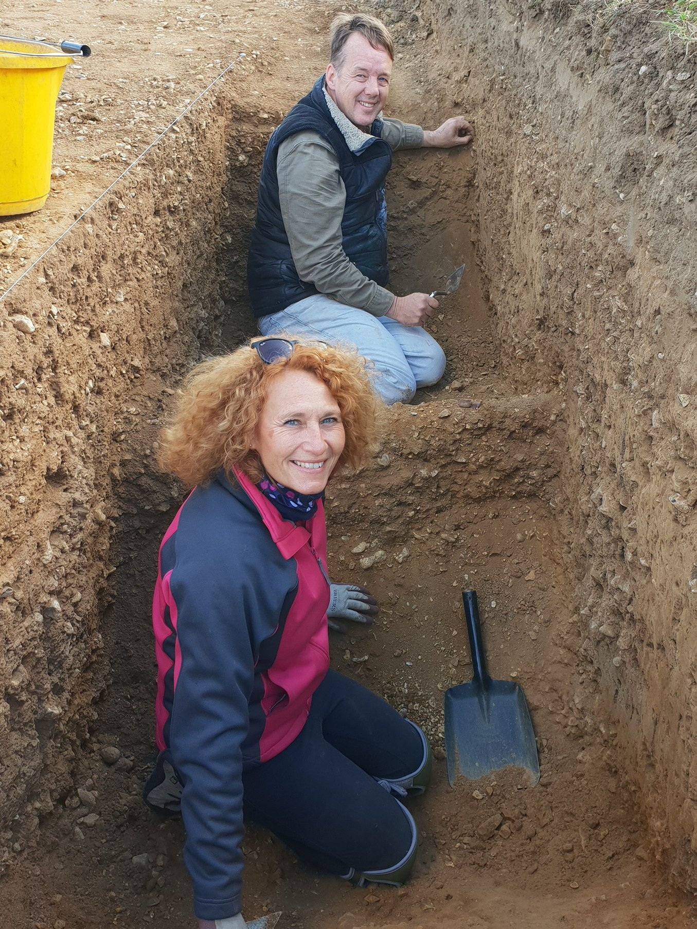 A man and a woman work in an excavation trench