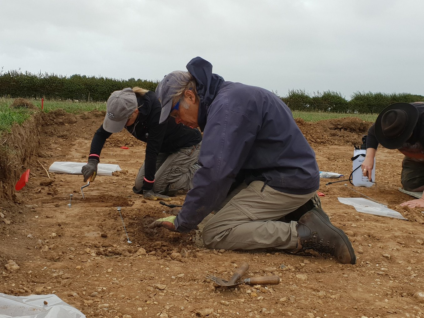 People working away at the ground of an excavation site