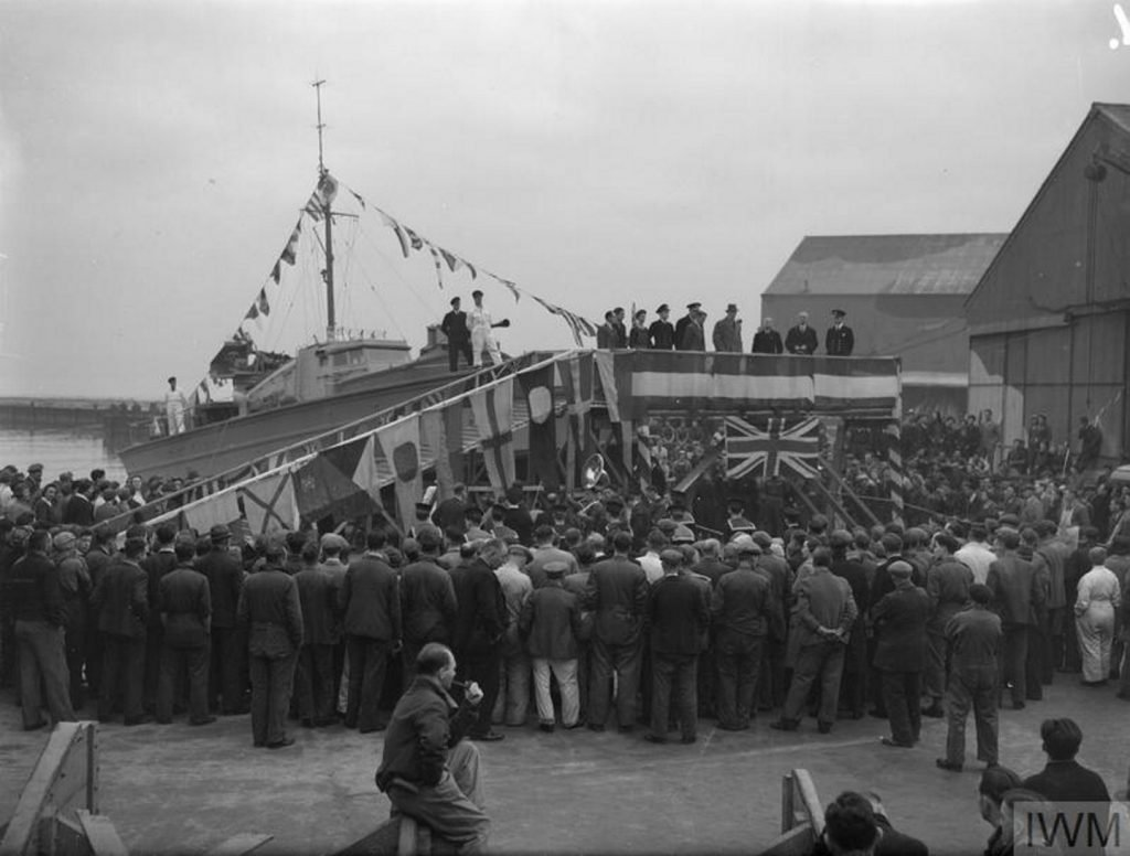 Hundreds of people gather around a boat about to be launched